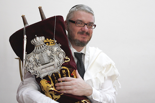 A photograph of Rabbi Paul Strasko holding a Torah scroll