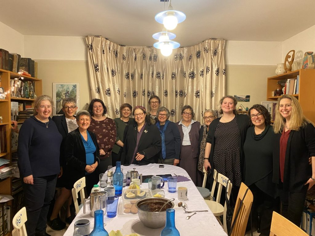 A photograph of 13 attendees attending a party in honour of Rabbi Dr Jackie Tabick