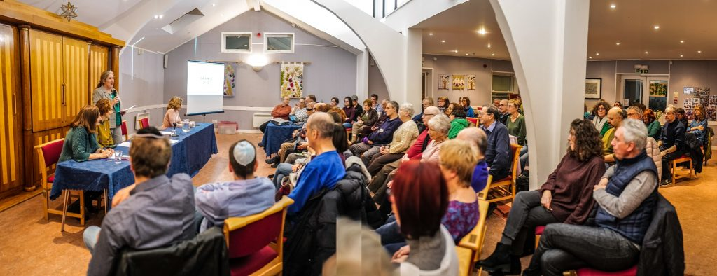 Rabbi Naomi addresses a packed hall at Kol Chai,  flanked by the Climate Change Panel