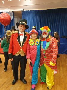 A photograph of three attendees dressed in circus attire